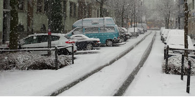 Snötäckt gata med bilar parkerade