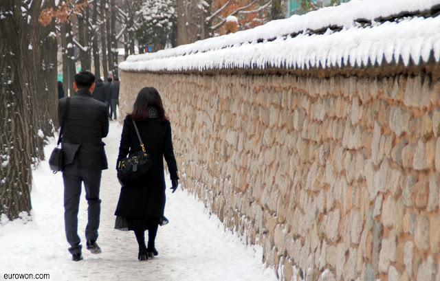 Pareja coreana paseando sobre la nieve