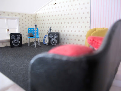 Interior of the first floor of a half-built Lundby dolls' house, with sofas and band equipment set up.