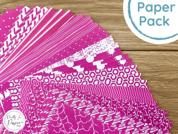 sample pack of patterned fuchsia paper sheets displayed on table