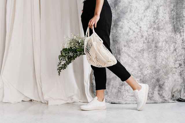 There is a girl in black trousers. She is walking across the image with a bag in her hand. The bag is a white reusable netting bag with flowers in