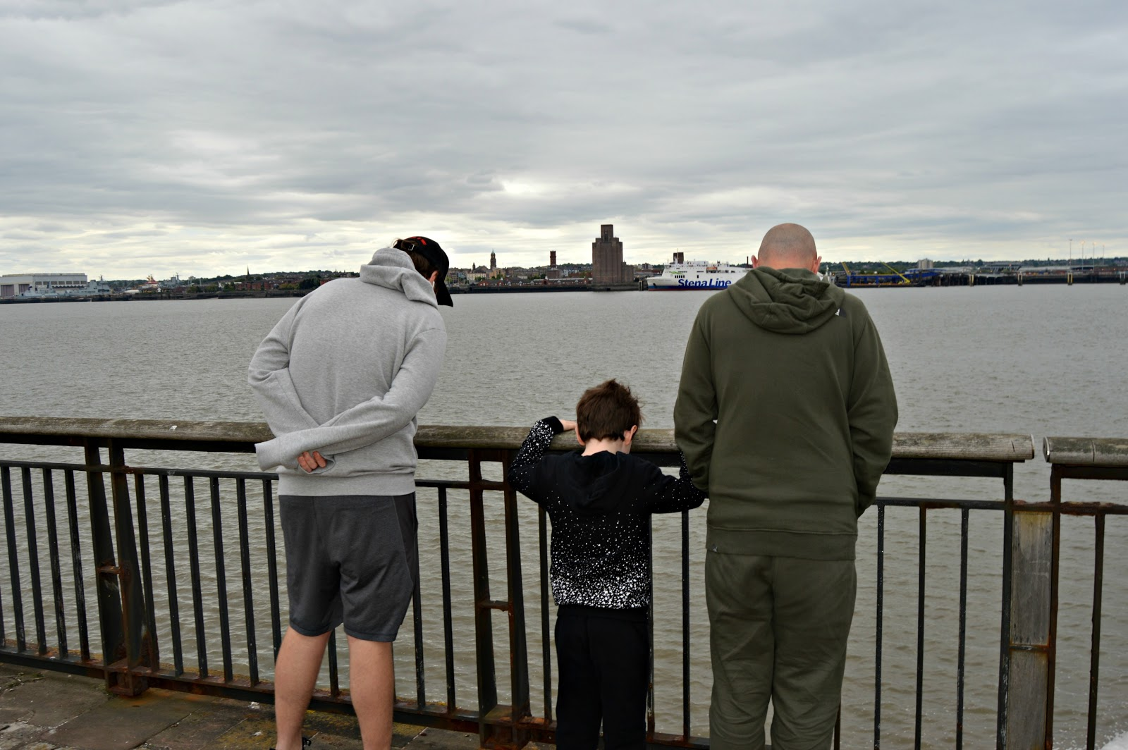 father and two sons looking out on to the sea