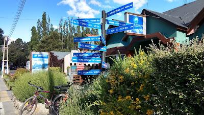"""Fotografia colorida retangular, horizontal. Um mastro com várias placas azuis em posições diversas, com letras brancas indicando nomes de glaciares e distâncias em quilômetros, em frente a uma casa de paredes verdes, entre vegetação florida de amarelo branco. Mais atrás, à esquerda, árvores de grande porte. Ao fundo, céu azul com tufos de nuvens brancas. Algumas das placas: """"GL. PERITO MORENO - ARG - 80 KM"""", GL. KOLKA - RUS - 15.251KM""""."""