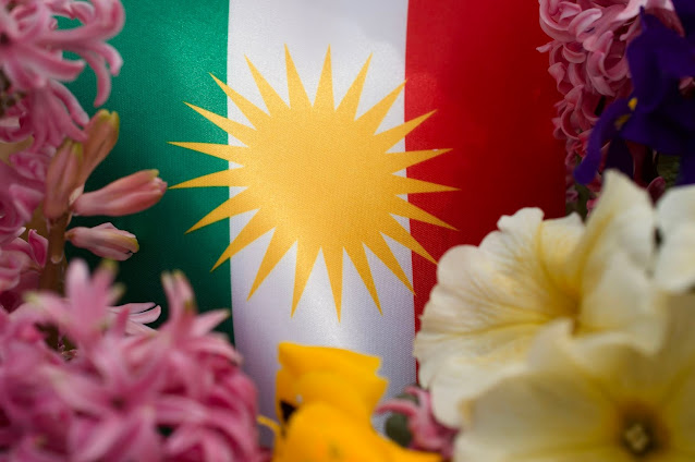 Kurdish Flag showing sun and Iran flag colors.