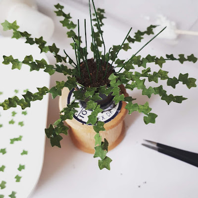1/12 scale miniature plant kit with half bare and half leafy stems in a plant pot filled with 'soil' on top of a cotton reel, with tray of extral leaves on one side and a pair of pliers on the other.