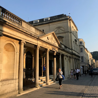 The 'King's Bath' entrance to the Roman Baths, Bath. There are Ionic columns in front of steps leading up to the door. The sun is shining on the building, making the yellow sandstone look even more golden.