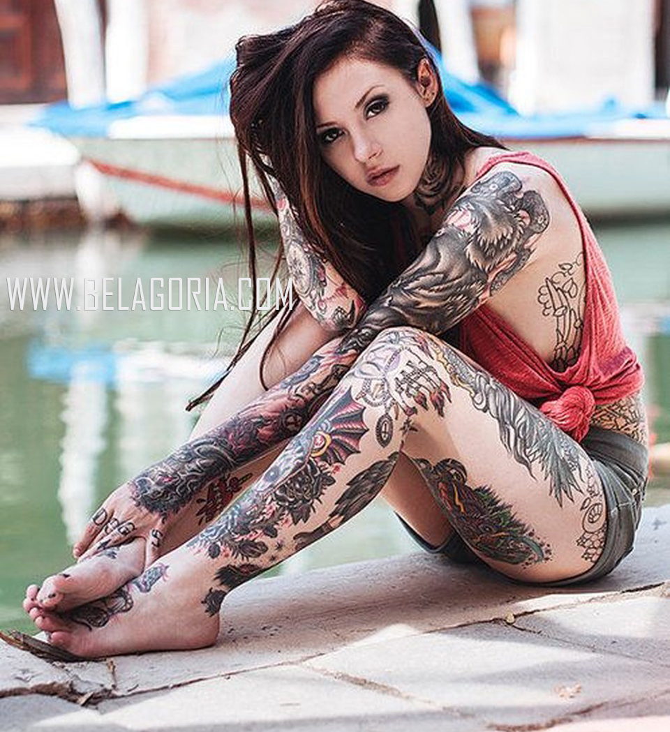 chica en un puerto deportivo nos mira , lleva tatuajes en todo el cuerpo y tatuaje en las piernas de estilo tradicional