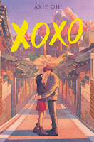 XOXO Book cover. A young woman and young man are standing facing each other with hands on the others' waist. They're in the street lined with traditional Korean buildings and the Seoul skyline is visible in the distance.