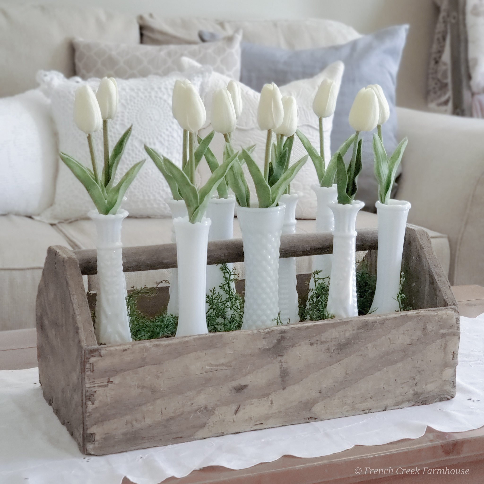 White tulips and milk glass vases in rustic wooden toolbox