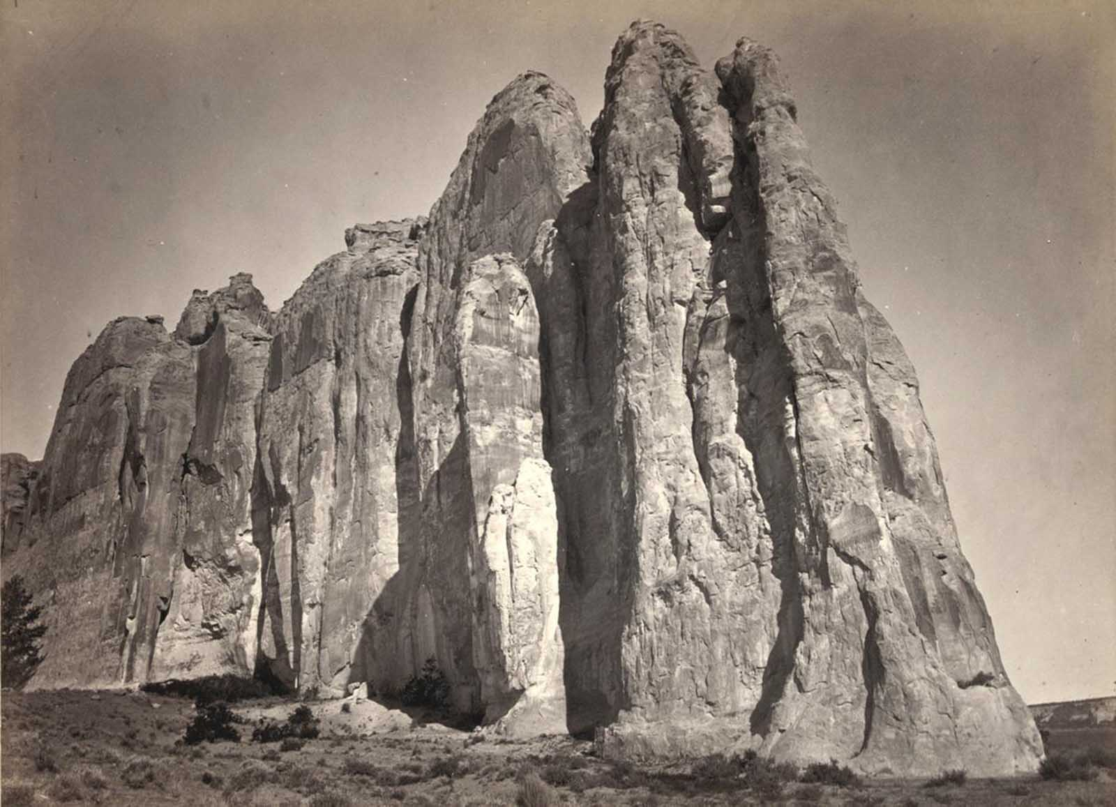The south side of Inscription Rock (now El Morro National Monument), in New Mexico in 1873. Note the small figure of a man standing at bottom center. The prominent feature stands near a small pool of water, and has been a resting place for travelers for centuries. Since at least the 17th century, natives, Europeans, and later American pioneers carved names and messages into the rock face as they paused. In 1906, a law was passed, prohibiting further carving.