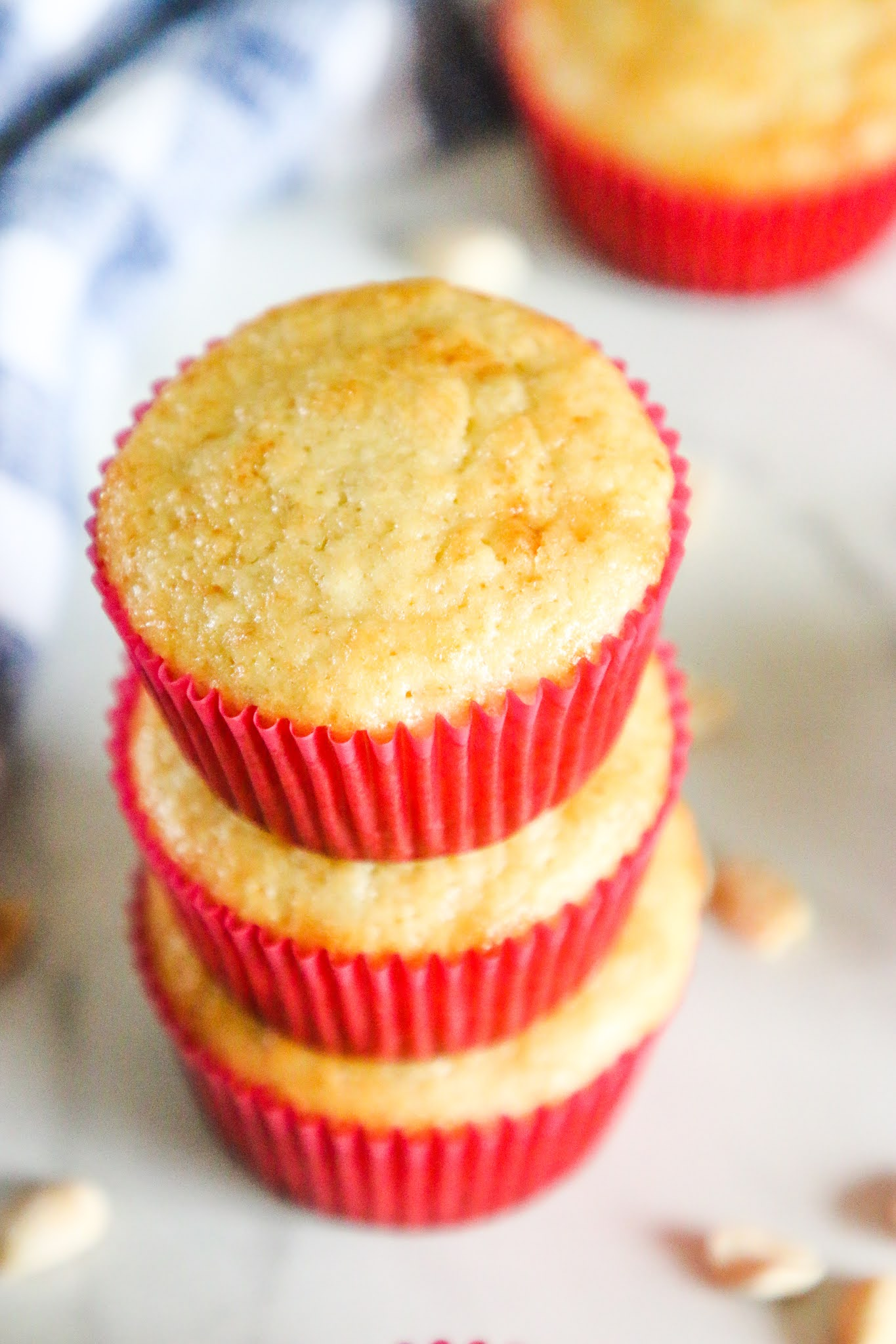 Three banana muffins stacked together on a marble table with a blue dish towel in the background.