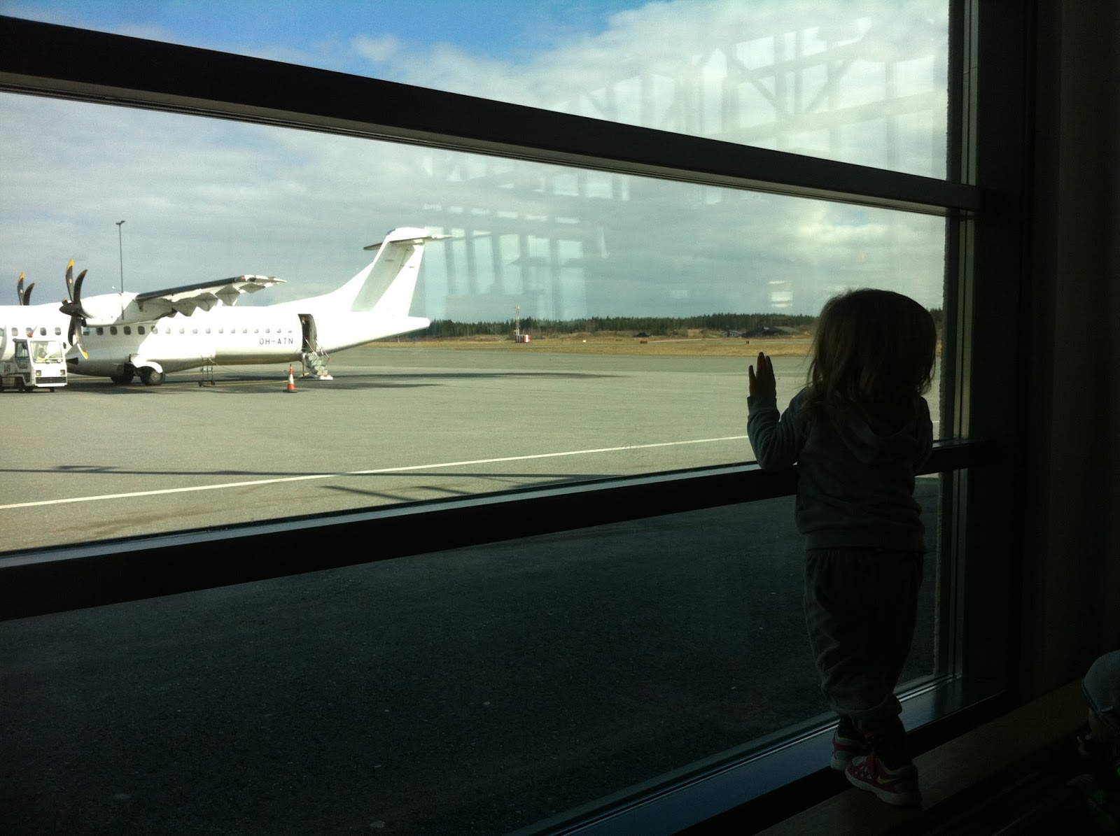 toddler standing and watching airplane at airport