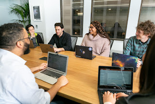 CC-BY-Mapbox-Uncharted-ERG_Mapbox-b024. Group of people in business casual, with their laptops, around a conference table. Group includes mix of genders, races and LGBTQ people.