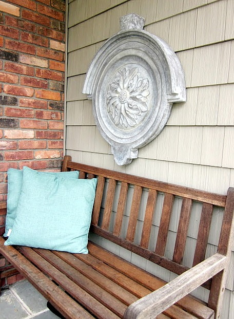 Teak bench with wall hanging and pillows