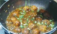 Sprinkling some chopped spring onions into veg manchurian gravy recipe