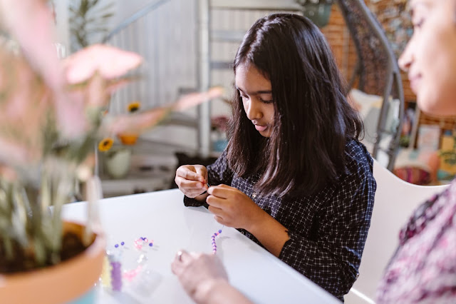 Girl working on a beaded jewelry.