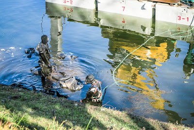 Sakurada Moat, Imperial Palace, Tokyo, Japan, with two divers doing repair work.
