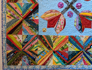 A lively mix of fabric strings sewn diagonally across each block form Xs around the border
