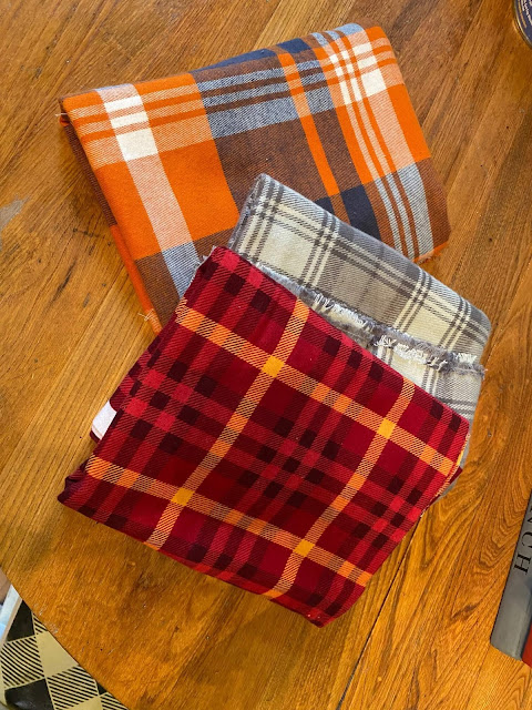 Photo of three folded squares of plaid flannel fabric.