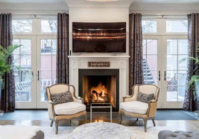 Living room with fireplace and luxury armchairs.