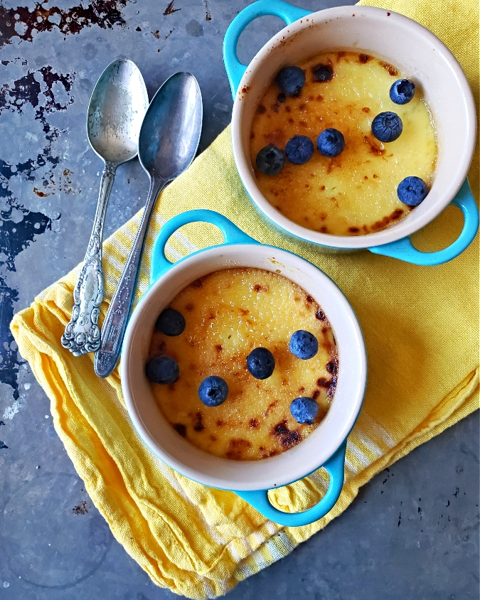 2 mini creme brulee desserts in Le Creuset with blueberries