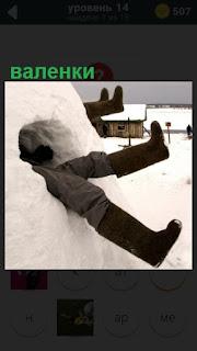из сугроба зимой торчат ноги обутые в валенки