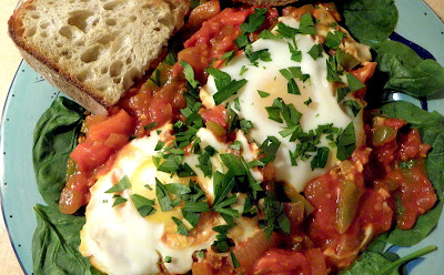 Shakshuka served over spinach with bread