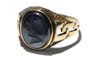 A golden and black color oval face ring.