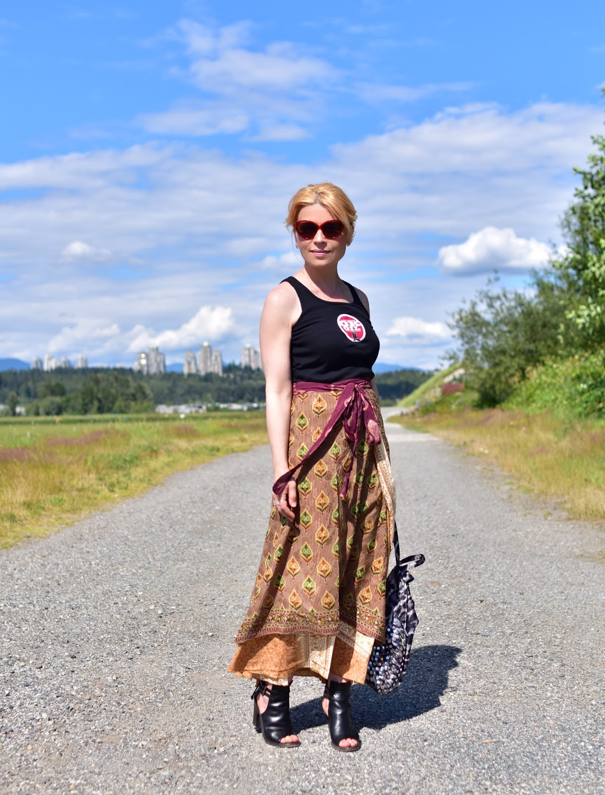 styling a silk wrap skirt with a graphic tank, cut-out booties, and a leopard-patterned backpack