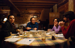 Four gamers sitting at a table playing Dungeons and Dragons. There are character sheets, dice, and pencils on the table, as well as empty food bowls and several empty (or almost empty) drink glasses, indicating that the game is at an end.
