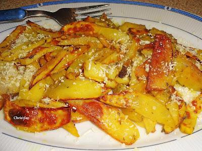 Πιατέλα με γαλαζιο περίγραμμα περιέχει ροδκοκινες πατάτες πασπαλισμένες με τυρί τριμένο,εχει και ενα πηρουνι