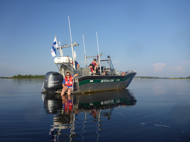 Tyynellä merellä veneessä on neljä henkeä T-paidoissa ja shortseissa