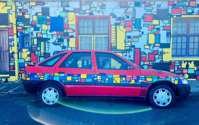 Car painted to match building mural in public art by Silas
