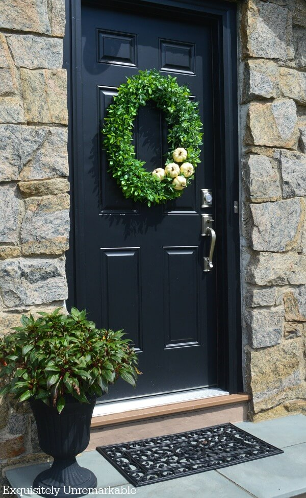 Black door, black planter, black mat with green boxwood pumpkin wreath on door