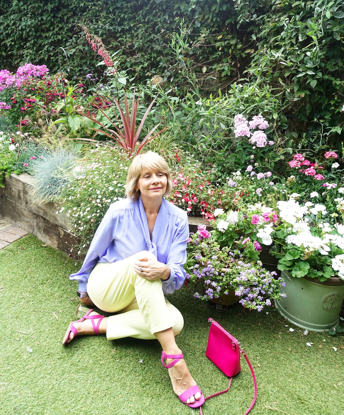 Seated pose in the garden for Is This Mutton's Gail Hanlon in her signature colour of lilac, worn here as a blouse with yellow trousers.