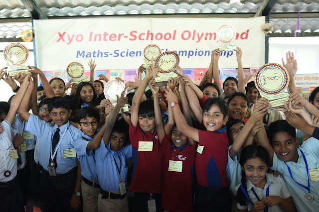 Excited students pose in front of the camera after winning trophies in the Olympiad.