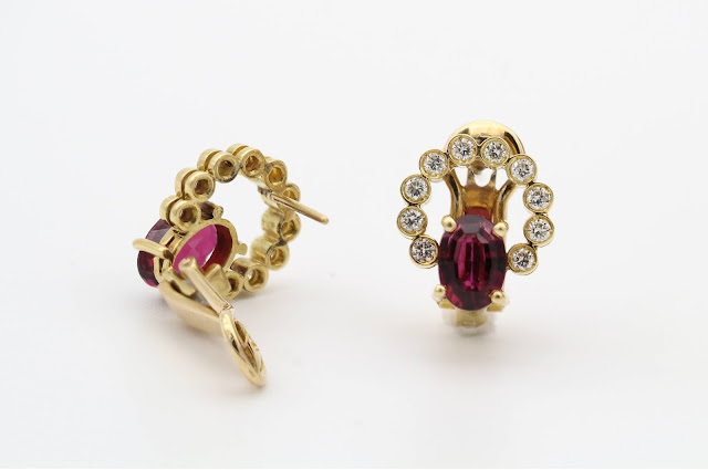 A pair of stud earrings with gemstones.