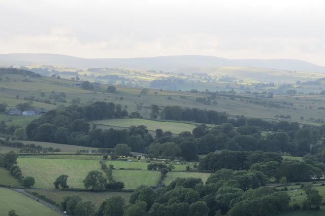 In the distance across farmland, the moors lie on the horizon.
