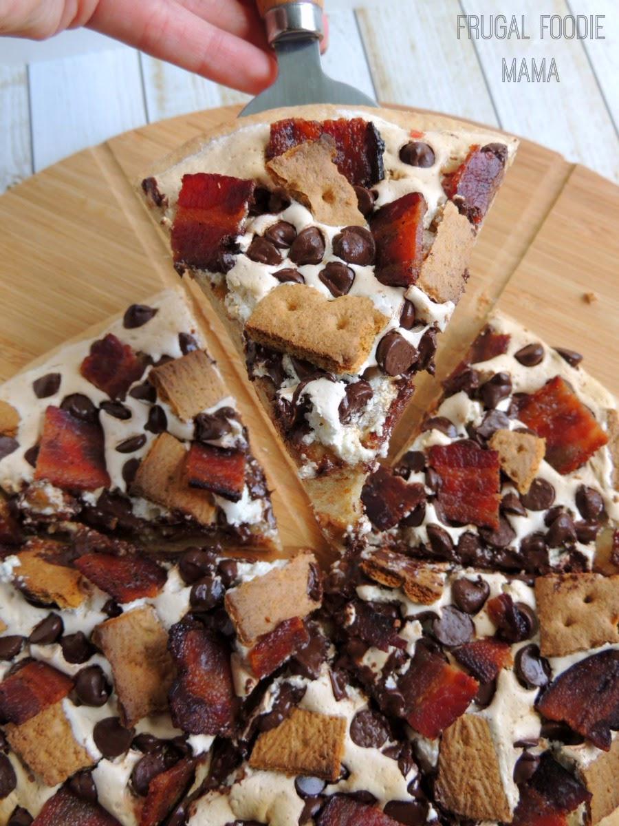 A soft, graham cracker pizza crust is topped with gooey marshmallow cream, chocolate chips, crunchy graham pieces, and smoky candied bacon in this Candied Bacon S'mores Pizza.