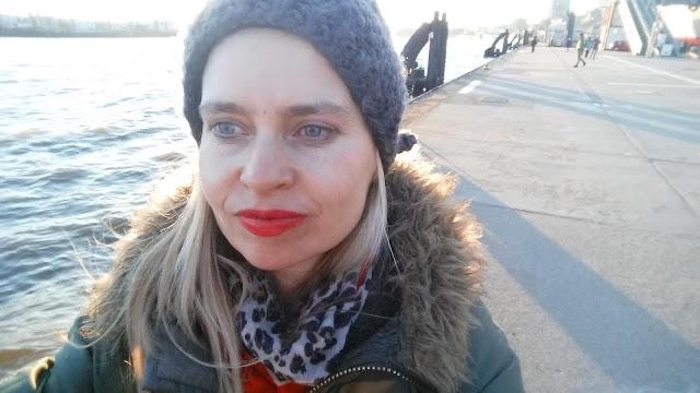 Jul Krabetz in Hamburg, grüner Parka, graue Mütze, roter Lippenstift