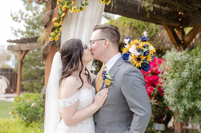 bride and groom kissing under a sunflower garland