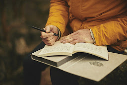 A person in a yellow jumper writing down their thoughts as part of a healthy habit in a book or journal