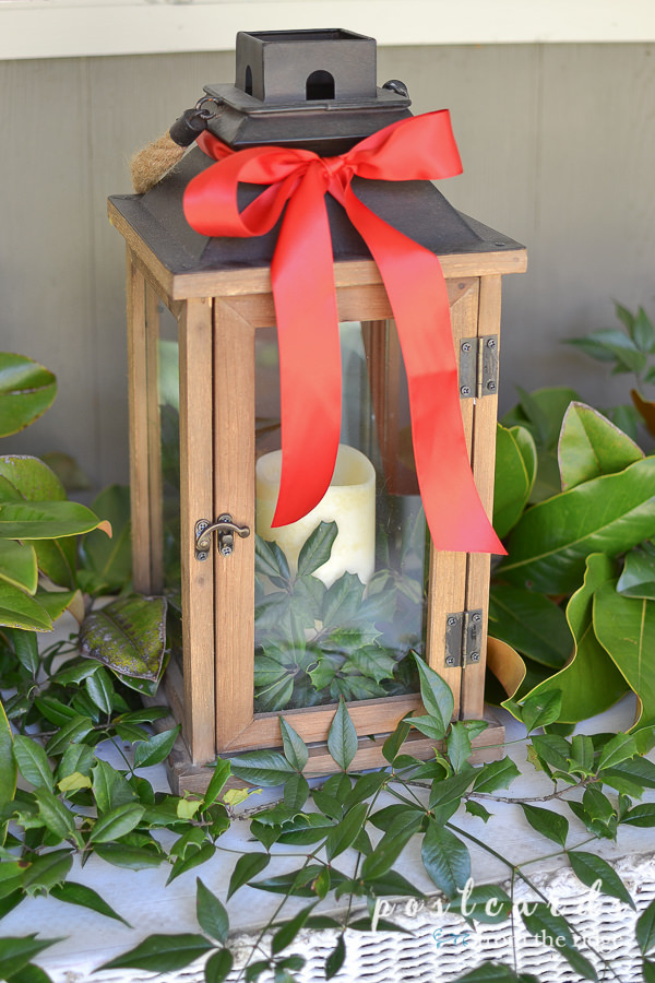 wooden lantern with fresh greenery and red satin ribbon