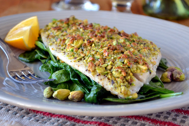 pistachio crusted flounder on a bed of baby spinach