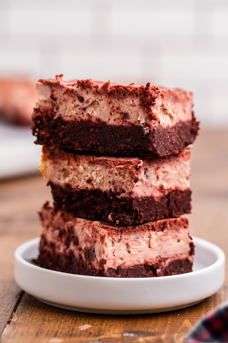 Closeup sideview of 3 Keto Red Velvet Cheesecake Brownies stacked on top of each other on a white plate.