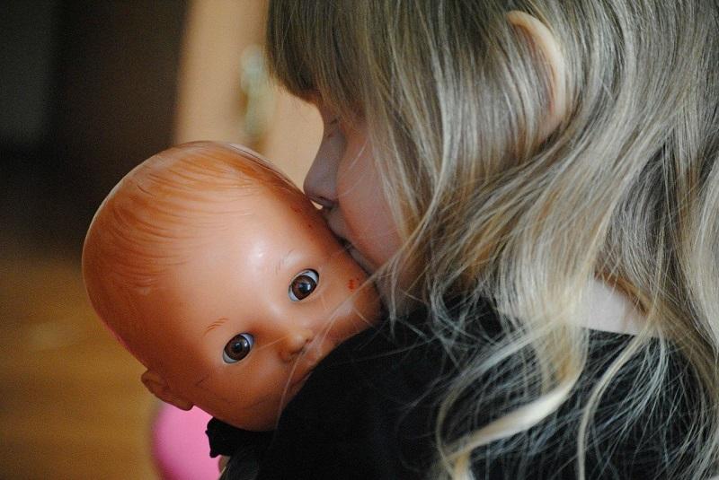 girl toddler kissing baby doll