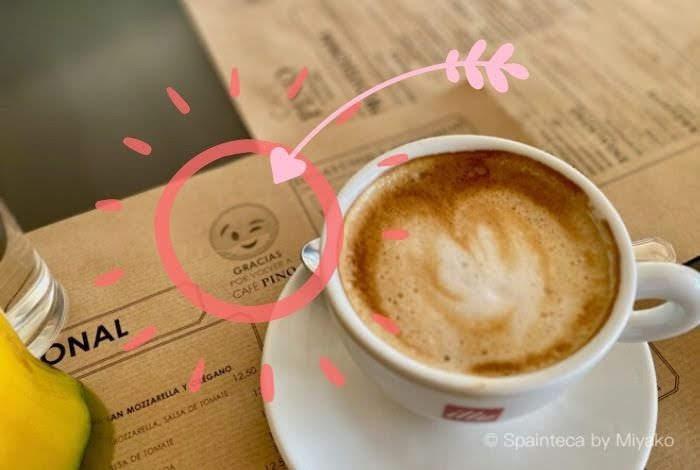マドリードのカフェでみつけたマスクをしたかわいい絵文字キャラとカフェ・コン・レチェ