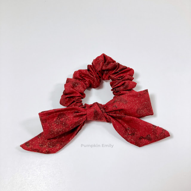A red scrunchie with a bow tied on it.