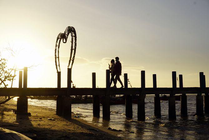 Siluet bingkai spot foto ala-ala dan pengunjung pantai Wates, Rembang