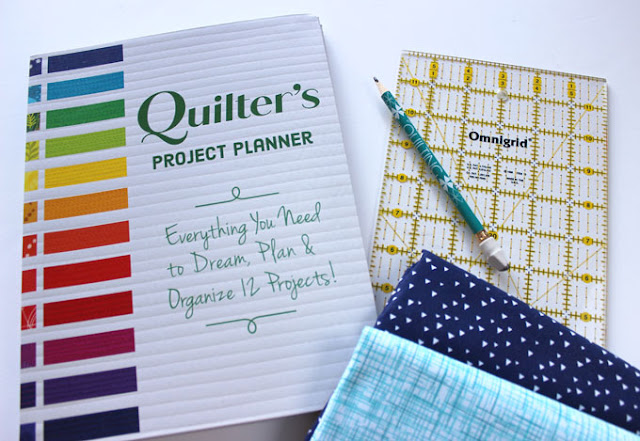 Quilter's Project Planner workbook with pencil and fabric closeby
